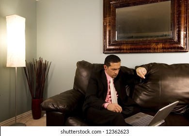 Home or Office - Businessman Looking at his Computer on the Couth