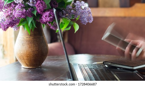 Home office concept. Woman working on a laptop, holding a smartphone in her hand near with a bouquet of lilacs
