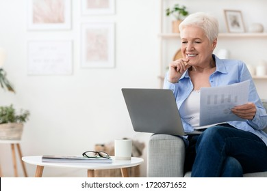 Home office. Confident senior business woman working with laptop and papers in living room, free space