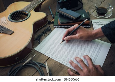 home office desk background, Desk musicians, hand holding pencil and writing note on wood table