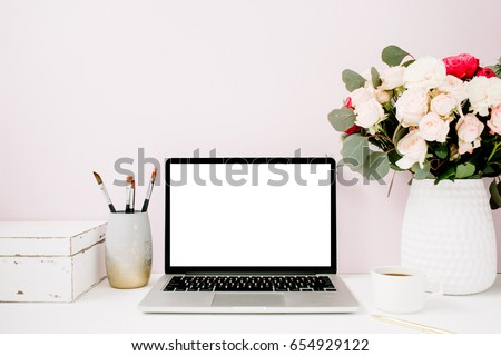 Home office desk with blank screen laptop, beautiful roses and eucalyptus bouquet, white vintage casket in front of pale pastel pink background. Blog, website or social media concept .