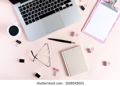 Home office desk with clip board, laptop, golden notepad, mug of coffee, paper clamps, calligraphic pen, watercolor cuvettes on a pale pink pastel background