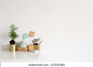 Home office desk with cork boxes, stationery, sticky notes and white wall for mock up or copy space.