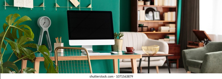 Home office desk with a desktop computer by a teal green wall in a designer apartment interior with books and record player