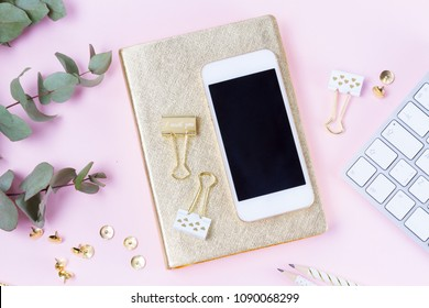 Home office desk with green eucaliptus and modern white phone on pink background