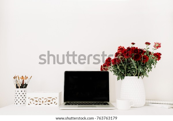 Home office desk with laptop, beautiful red flowers bouquet, white vintage casket in front of white background. Blog, website or social media concept .