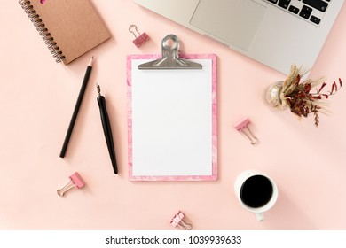Home office desk with laptop, clip board, kraft notepad, bouquet of dry flowers, calligraphic pen, pencil, paper clips, mug of coffee on a pink pastel background