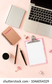Home office desk with laptop, clip board, notepads, bouquet of dry flowers, calligraphic pen, pencil, paper clips, mug of coffee on a pink pastel background