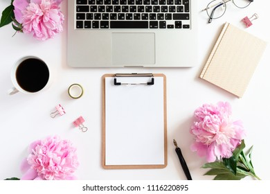 Home office desk with laptop, clip board, golden notepad, pink peonies, mug of coffee, stationery, glasses on a white background