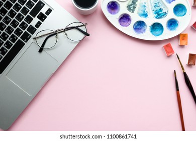 Home office desk with laptop, glasses, mug of coffee, watercolor cuvette, palette, paint brushes on a pink pastel background