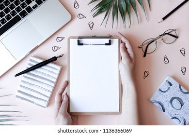 Home office desk with laptop, glasses, stationery, notepads, green leaves. Girl  hands hold a clip board on a pale pink background