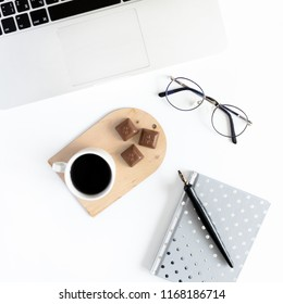 Home office desk with laptop, glasses, silver notepad, calligraphic pen, mug of coffee, chocolate on a white background