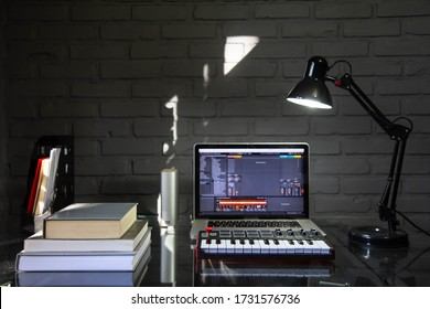 Home office desk with midi keyboard, notebook and books.