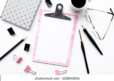 Home office desk with pink clip board, glasses, silver notepad, mug of coffee, paper clamps, paint brush, calligraphic pen on a white background