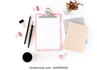 Home office desk with pink clip board, notepads, bouquet of dry flowers, calligraphic pen, pencil, paper clips, mug of coffee on a white background