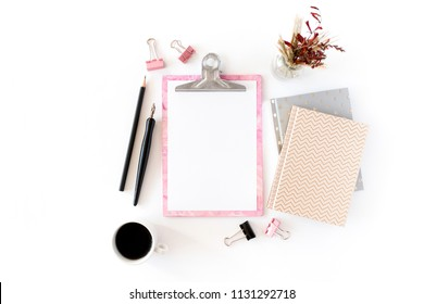 Home office desk with pink clipboard, notepads, bouquet of dry flowers, calligraphic pen, pencil, paper clips, mug of coffee on a white background