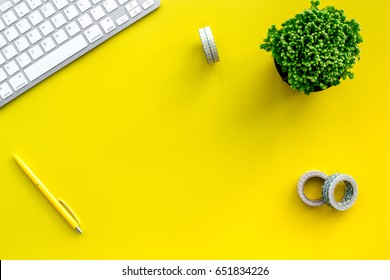 home office desk with plants, sticky tape and keyboard on yellow background top view mock up