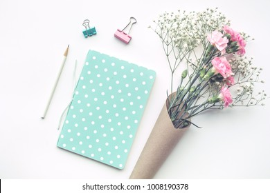 Home office desk table with notepad,flower on white background.Flat lay.feminine concepts design.minimalist style