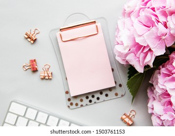 Home office desk workspace with blank paper clipboard, pink hydrangea flowers bouquet on white background. Flatlay