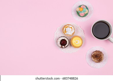 Home office desk. Workspace with coffee and cupcake. Flat lay, top view on pink background. Coffee break.