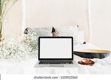 Home office desk workspace with laptop with blank screen, vintage saucer, white flowers. Front view mock up template. Blog hero header interior concept.