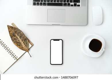 Home office desk workspace with mockup of mobile phone with blank white screen, laptop, cup of coffee, notebook on white background. Flat lay, top view modern minimalist blog header template.