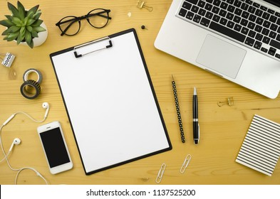 Home office desk workspace with with silver notebook, smartphone and office accessories on wood desk background.