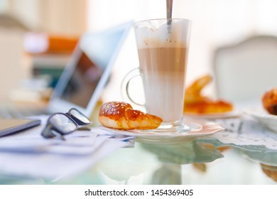 Home office, ideal working environment with breakfast. Luxury interior, glass table, reflection, notebook, eyeglasses, mobile phone and blurred background. Wellbeing at work.
