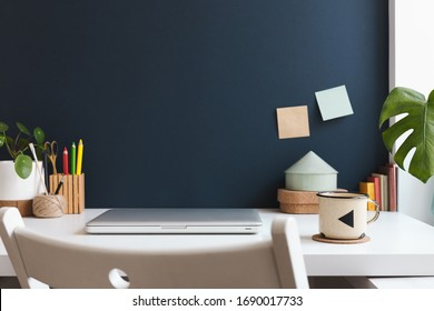 Home office with laptop closed, office supplies, mug, notes, books and dark blue wall. Homeschooling concept. Trendy, creative workspace.