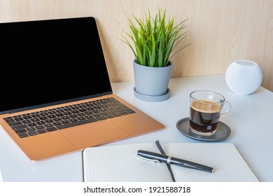 Home office. Laptop with empty screen, pen, notebook, cup of coffee and smartphone