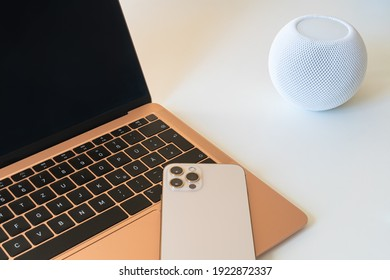 Home office. Laptop with empty screen, smart speaker and mobile phone on keyboard.