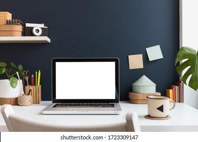 Heimbüro mit Laptop-Modell, Vorräte, Kaktus und Bücher in der Nähe der blauen Mauer. Konzept des Heimunterrichts. Trendy, kreativer Schreibtisch.