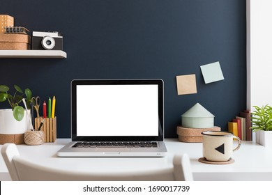 Home office with laptop stationery, cactus and books near navy blue wall. Home learning concept. Trendy, creative desk.