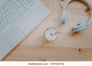 Home office. Quiet workspace with coffee, laptop and headphones. Work away. Relax and disconnection moment with chill music. Top view.