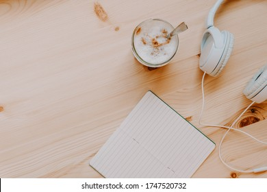 Home office. Quiet workspace with coffee, headphones and a notebook. Work away. Relax and disconnection moment with chill music. Top view.