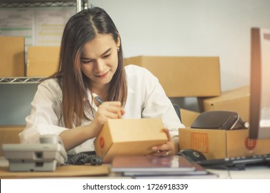 Home office and startup of small business owner businesswoman, delivery shipping package with parcels,cardboard box and writing addresses to deliver customer from online order to e-commerce businesses