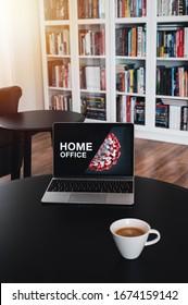 Home office theme. Home office during coronavirus pandemic. Novel coronavirus 2019 COVID-19 theme. Coronavirus wallpaper on computer. Coffee Cup in foreground.