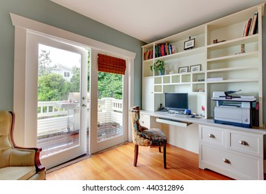 Home office with white open shelves, hardwood floor and blue walls.