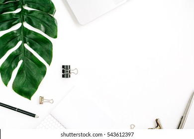 Home office workspace frame with laptop, palm leaf and accessories. Flat lay, top view
