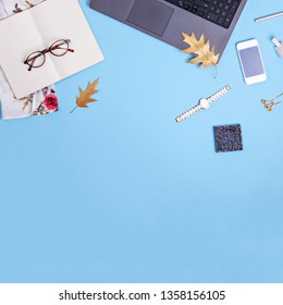 Home office workspace with laptop, glasses and dress on blue background. Fashion blogger work concept. Flat lay