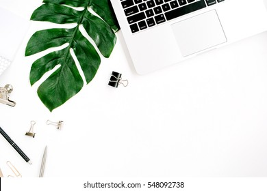 Home office workspace with laptop, palm leaf and accessories. Flat lay, top view