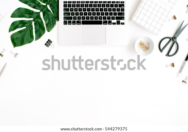 Home office workspace with laptop, palm leaf, notebook and accessories. Flat lay, top view
