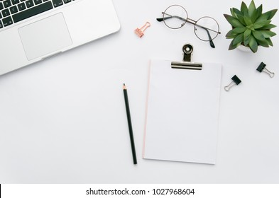 Home office workspace mockup with laptop, clipboard, green plant, notebook and eyeglasses, with copy space background. Flat lay, top view