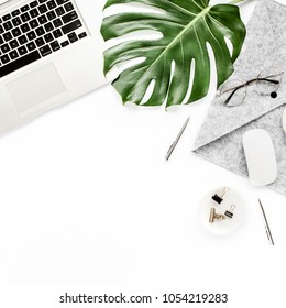 Home office workspace mockup with laptop, tropical leaves Monstera, notebook and accessories on white background. Flat lay, top view