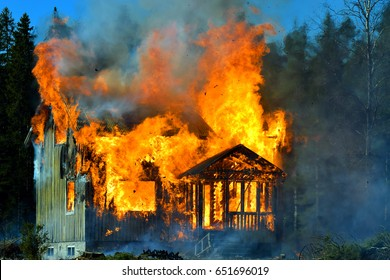 Home on fire as the flames burst through the windows, door and roof of the house