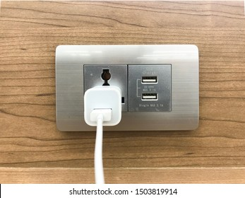 The home outlet is plugging in a smartphone charger.