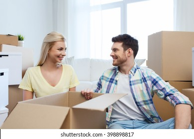 home, people, repair and real estate concept - smiling couple with many cardboard boxes moving to new place