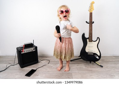 Home performance: A young girl sits on the floor singing with a microphone. Nearby stands music equipment.