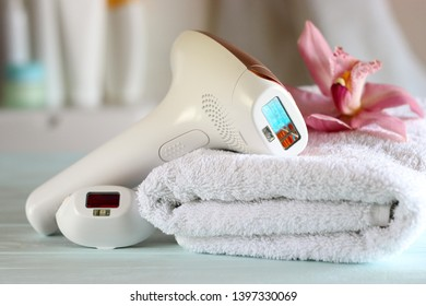 Home photoepilator to remove unwanted body hair against the background of the bathroom interior.
