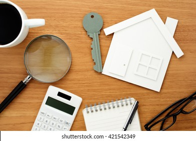Home planning. Calculating and checking. House and key shaped paper cutout, calculator and magnifier on wooden table.